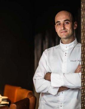 Portrait américain d'un chef en veste de cuisine dans la salle de son restaurant
