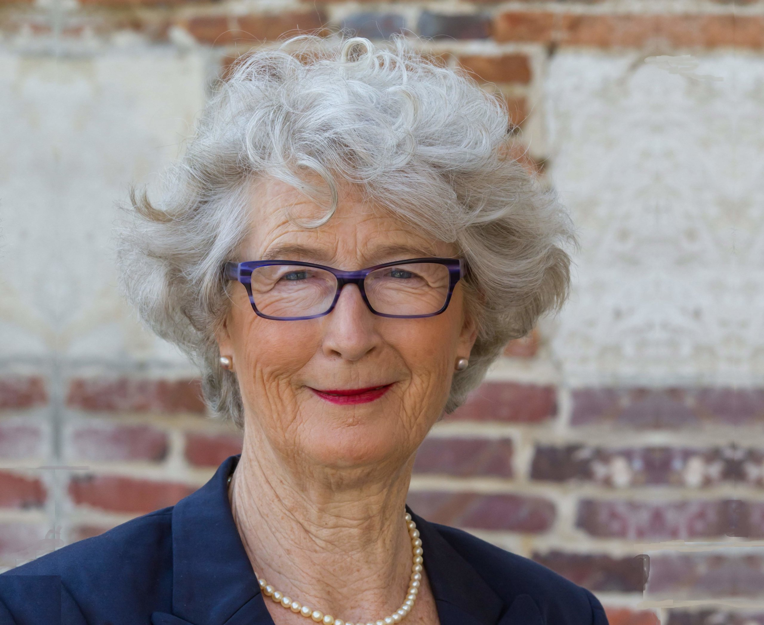 Portrait femme cheveux gris, blazer bleu marine et collier de perles