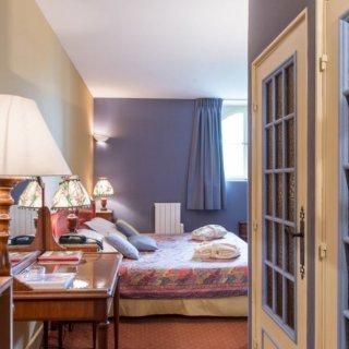 Vue sur un lit deux places dans une chambre avec en premier plan des lampes de chevets contre le mur