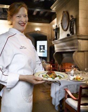 la restauratrice Marine tenant en veste de cuisine tenant présentant un de ses plats entre ses mains