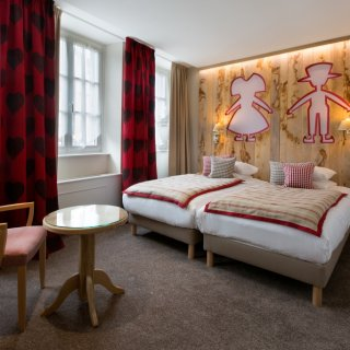 Chambre double avec deux lits simples, les têtes de lits sont des panneaux de bois dans lesquels sont découpés des personnages
