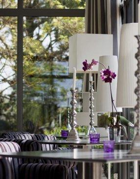 Plan de plusieurs tables en verres sur lesquelles sont disposés des fleurs et des bougeoires