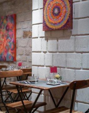 Table et chaises en bois devant un pan de mur en briques blanche, service pour deux personnes dressé