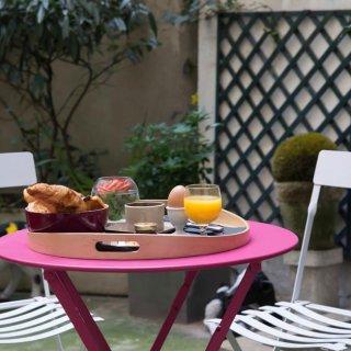Table en métal rose dépliée avec petit déjeuner sur un plateau et derrière deux chaises de jardin blanches dépliées