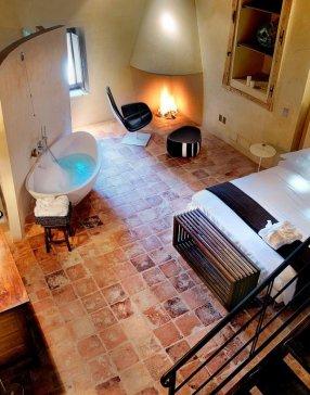 Vue de haut d'une chambre avec baignoire, lit double avec draps blanc et plaide marron