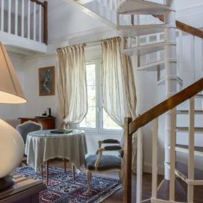 Chambre en dupleix, avec petit salon au rez-de-chaussée, fauteuils crapauds en velours et un escalier hélicoïdal menant à la mezzanine