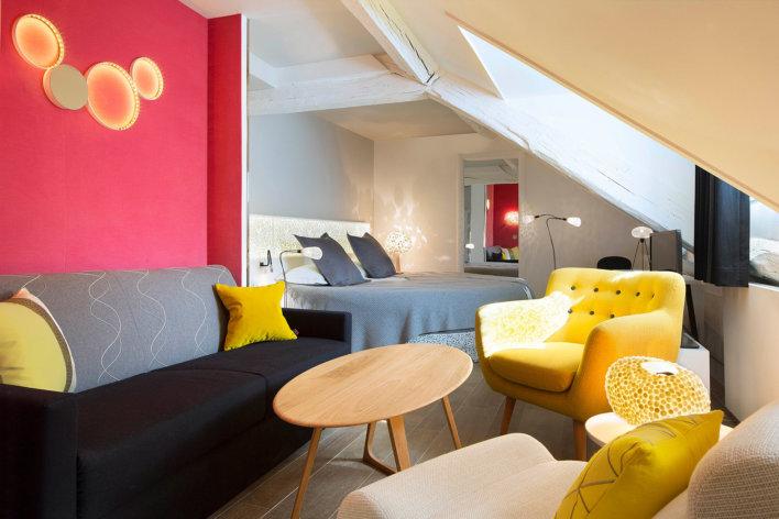 Chambre avec lit rond, un mur rose framboise et quelques éléments de décoration jaune, gris et bois. Chambre mansardée