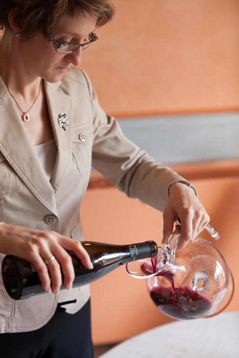 Femme versant du vin rouge dans une carafes à décanter