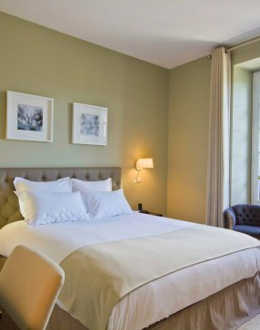 Chambre avec lit double agencée avec 2 fauteuil de style crapaud et bureau