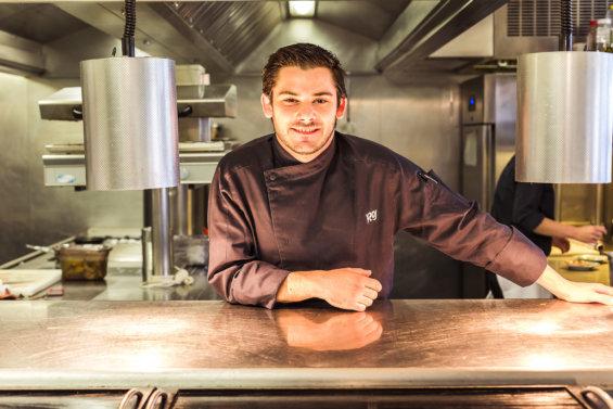 Portrait d'un chef en veste de cuisinier dans sa cuisine derrière un plan de travail