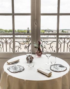 Table dressée pour deux couverts avec vue sur une grande place