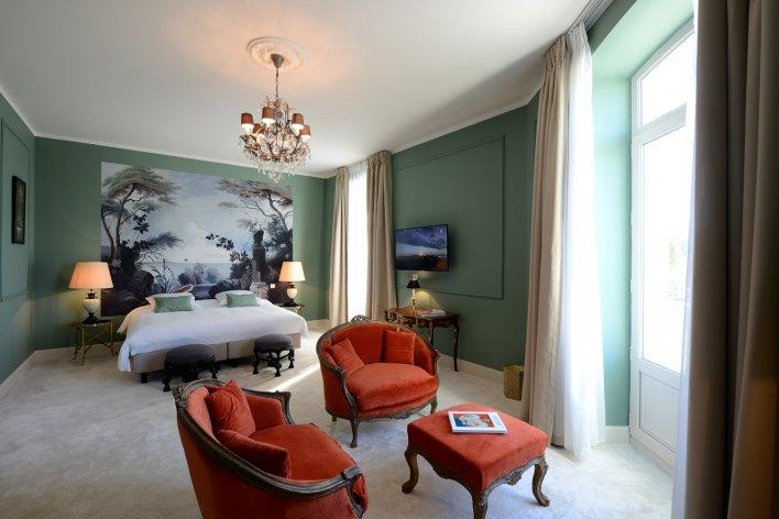 Chambre lit double tête de lit paysage et petit coin salon fauteuils rouges