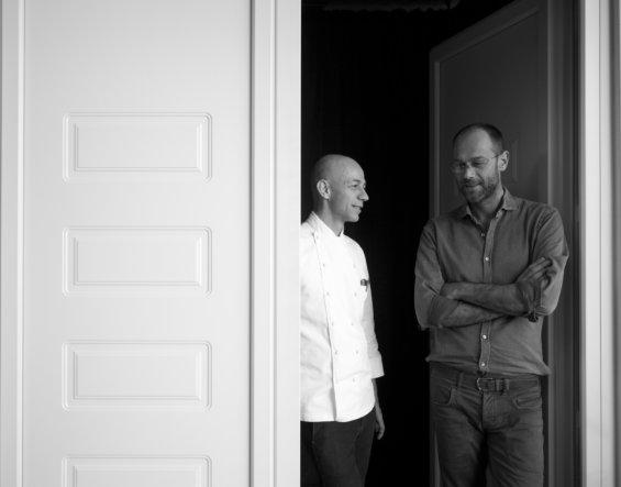 Un chef en veste de cuisinier contre une porte blanche en face d'un homme serveur en chemise noir contre une autre porte, photo noir et blanc