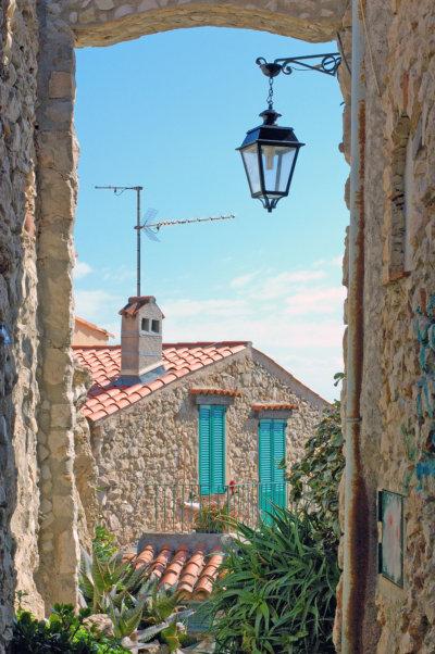 Vue sur une maison typique provençale depuis une fenêtre ouverte sur une ruelle