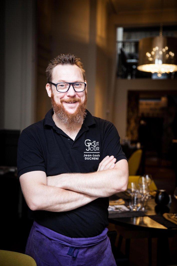 Chef en t-shirt noir et tablier mauve, dans un salle de restaurant