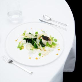Plat de poisson dans une assiette, sur une table nappée blanche et couverts argentés