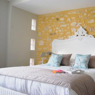 Chambre lit double, mur peinture jaune et pierres apparentes