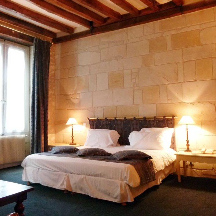 Chambre avec poutres apparentes et mur en pierre de tuffeau