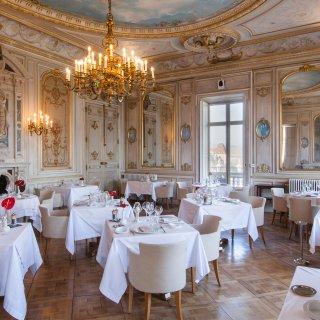 Salle de restaurant chic, avec tables dressées, plafond peint et lustre