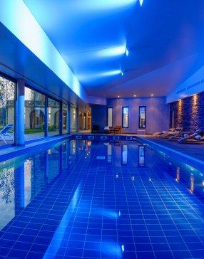 Grand piscine chauffée couverte avec espace bien-être en arrière-plan