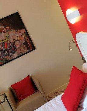 Chambre avec tête de lit romantique, mur rouge, décoration de tableaux colorés