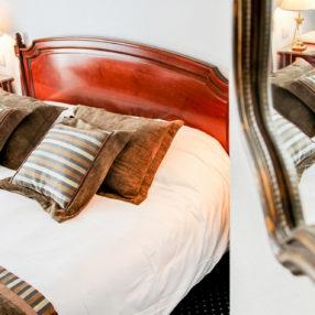 Gros plan sur un miroir reflétant un lit double dans uns chambre de charme
