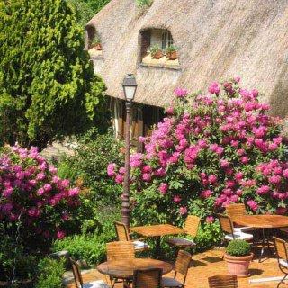 Terrasse avec table et chaises en bois arrière plan ancienne bâtisse toit en chaume