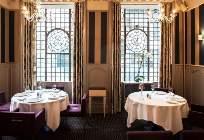 Salle de restaurant avec deux tables dressées face à deux grandes fenêtres