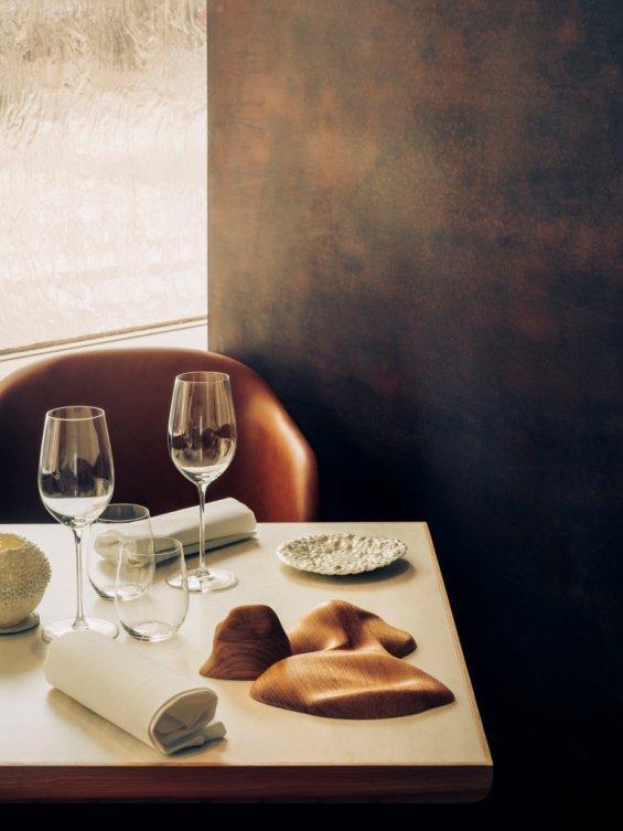 Deux couverts dressés sur une table avec mur couleur bronze