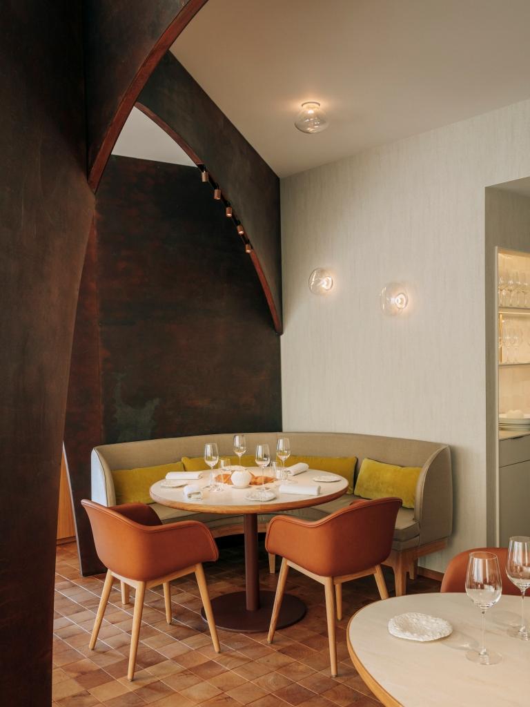 Quatre couverts dressés sur une table avec mur couleur bronze