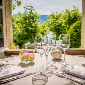 Table dressée devant une fenêtre ouverte avec vue sur le lac d'Annecy
