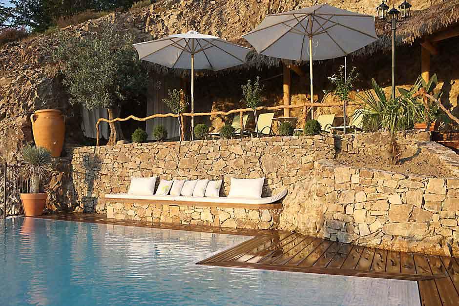 Terrasse avec transat et parasol devant piscine