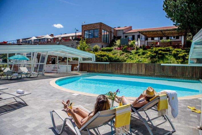 terrasse en bois et piscine avec transat et deux femmes