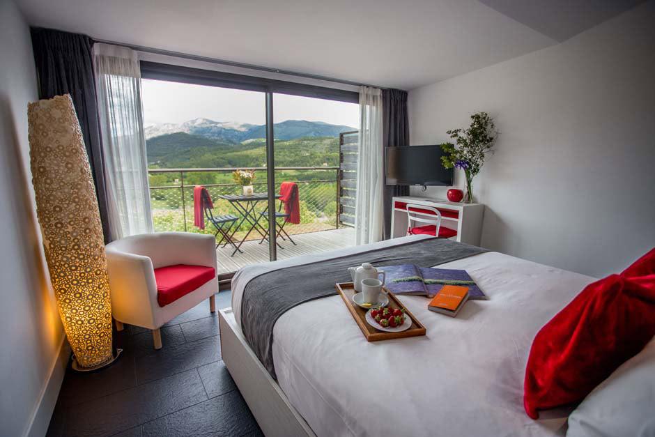 chambre lit double avec fauteuil et meuble tv devant grande baie vitrée