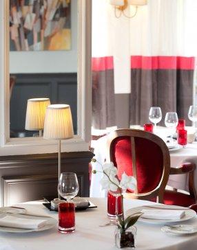 Salle de restaurant avec tables dressées, équipée de sièges en velours rouge