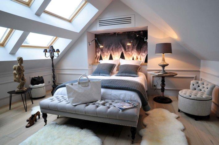 Chambre lit double avec tableau autour du champagne au mur, grandes fenêtres, linge de lit et décoration dans les gris, beiges et blancs