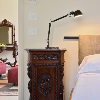 Zoom table de chevet tête de lit linge blanc et arrière plan coiffeuse et fauteuil rouge