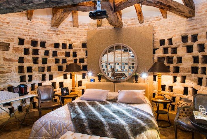 Chambre installée dans un ancien pigeonnier avec perites niches tout autour et miroir à la tête du lit