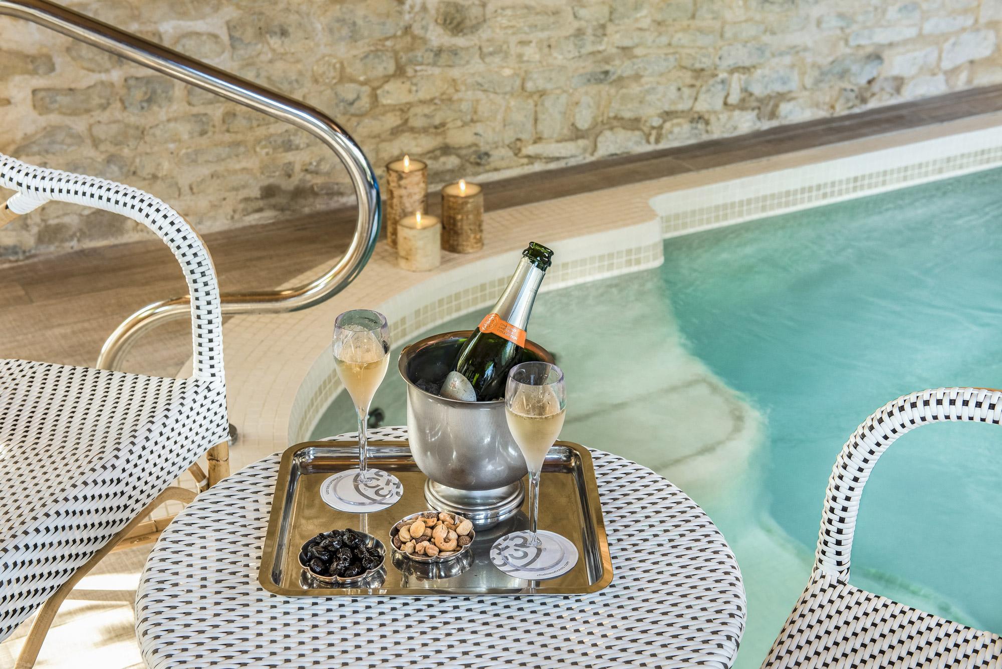 Bouteille de Champagne avec coupes servies sur une table près d'un jacuzzi privatif
