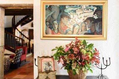 Salon avec tableau de peinture accroché au dessus d'un buffet bas et escalier en bois à l'arrière plan