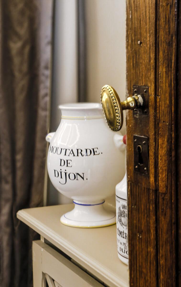 Grand pot de moutarde de Dijon en porcelaine posé sur un meuble ancien avec porte entrouverte en premier plan