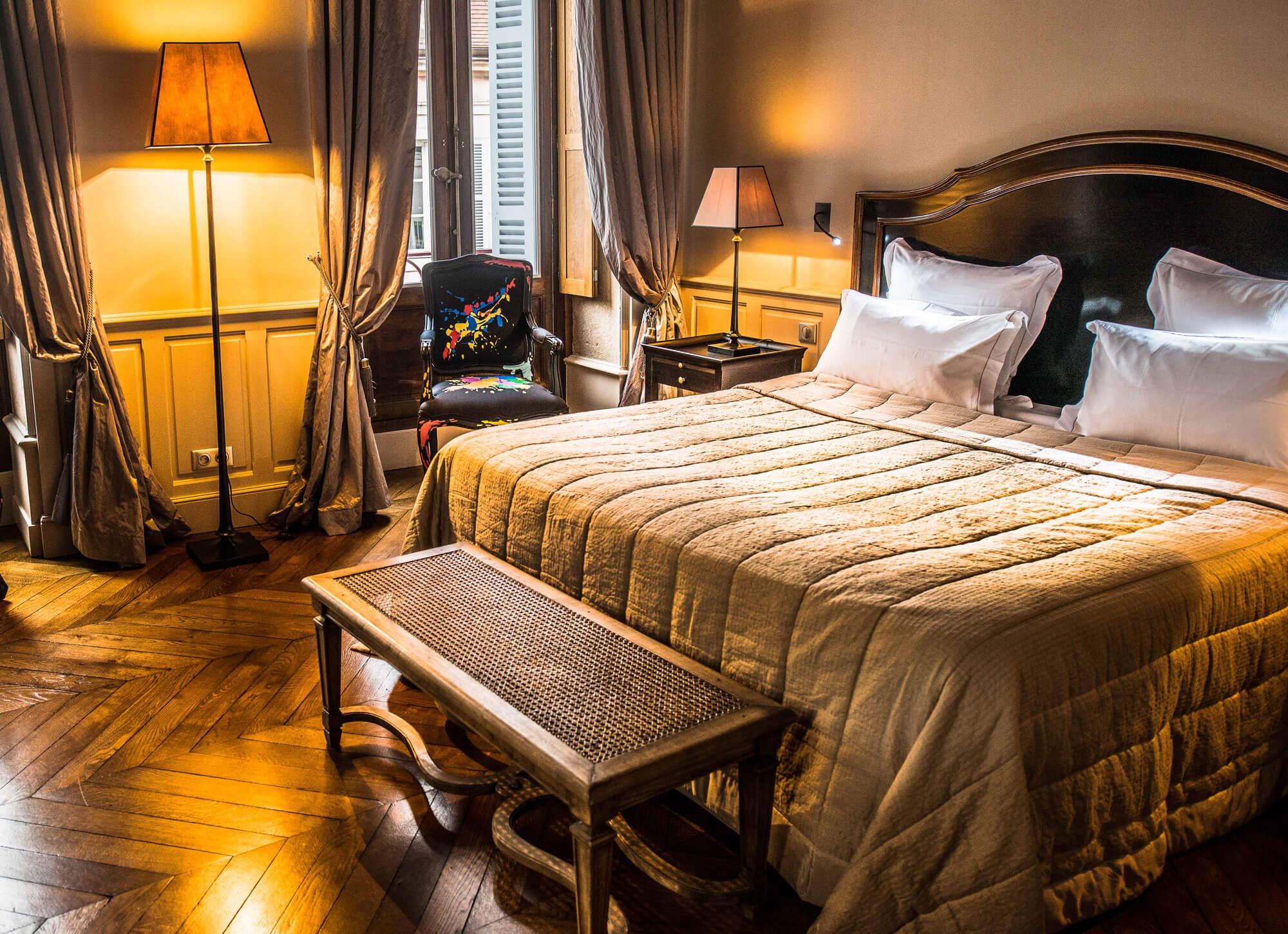 Chambre avec lit en bois ancien et banc au pied du lit
