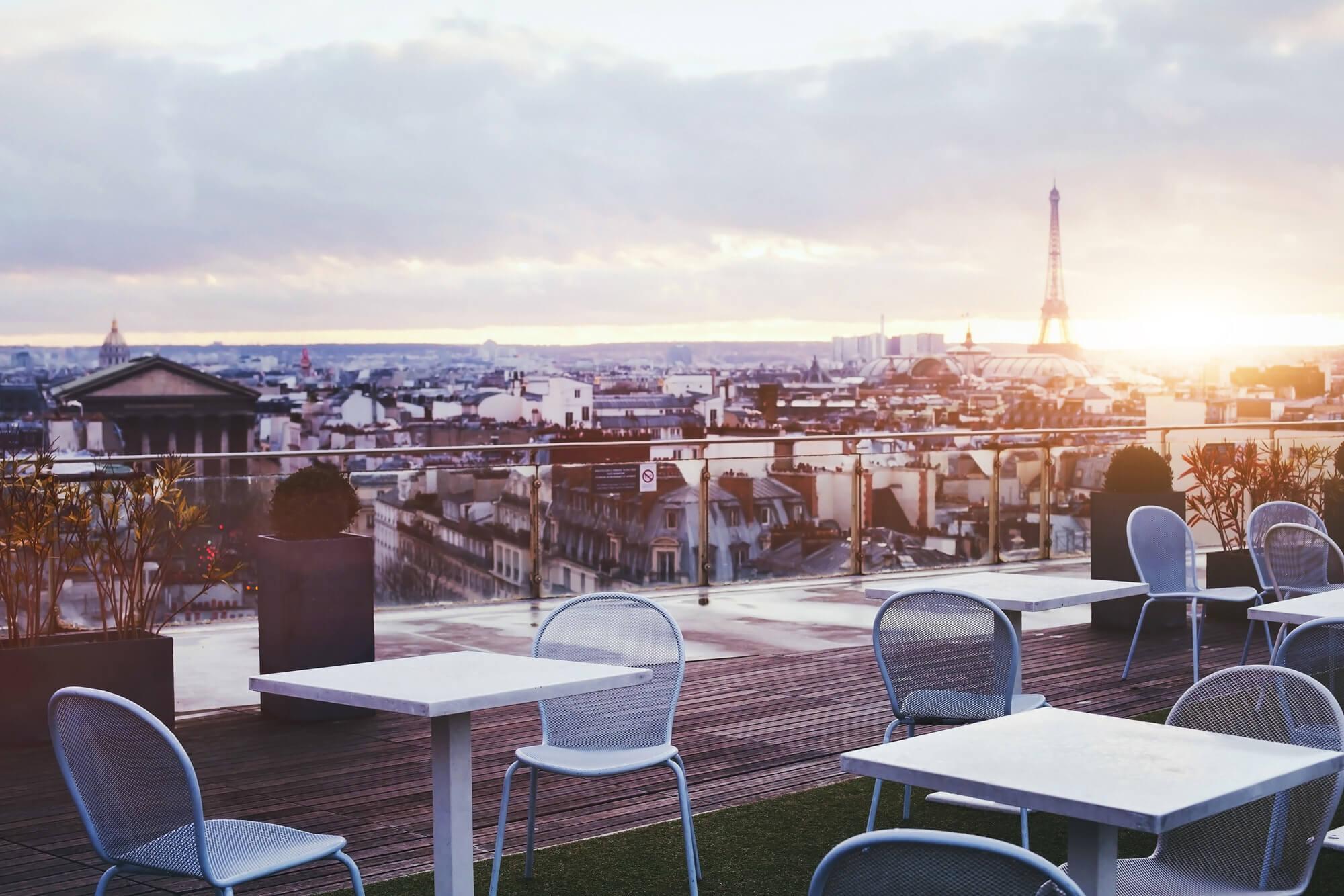 Photo prise d'une terrasse de laquelle on aperçoit les toits de Paris et la Tour Eiffel
