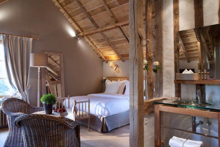 Chambre romantique avec poutres apparentes à l'Auberge de la Source en Normandie