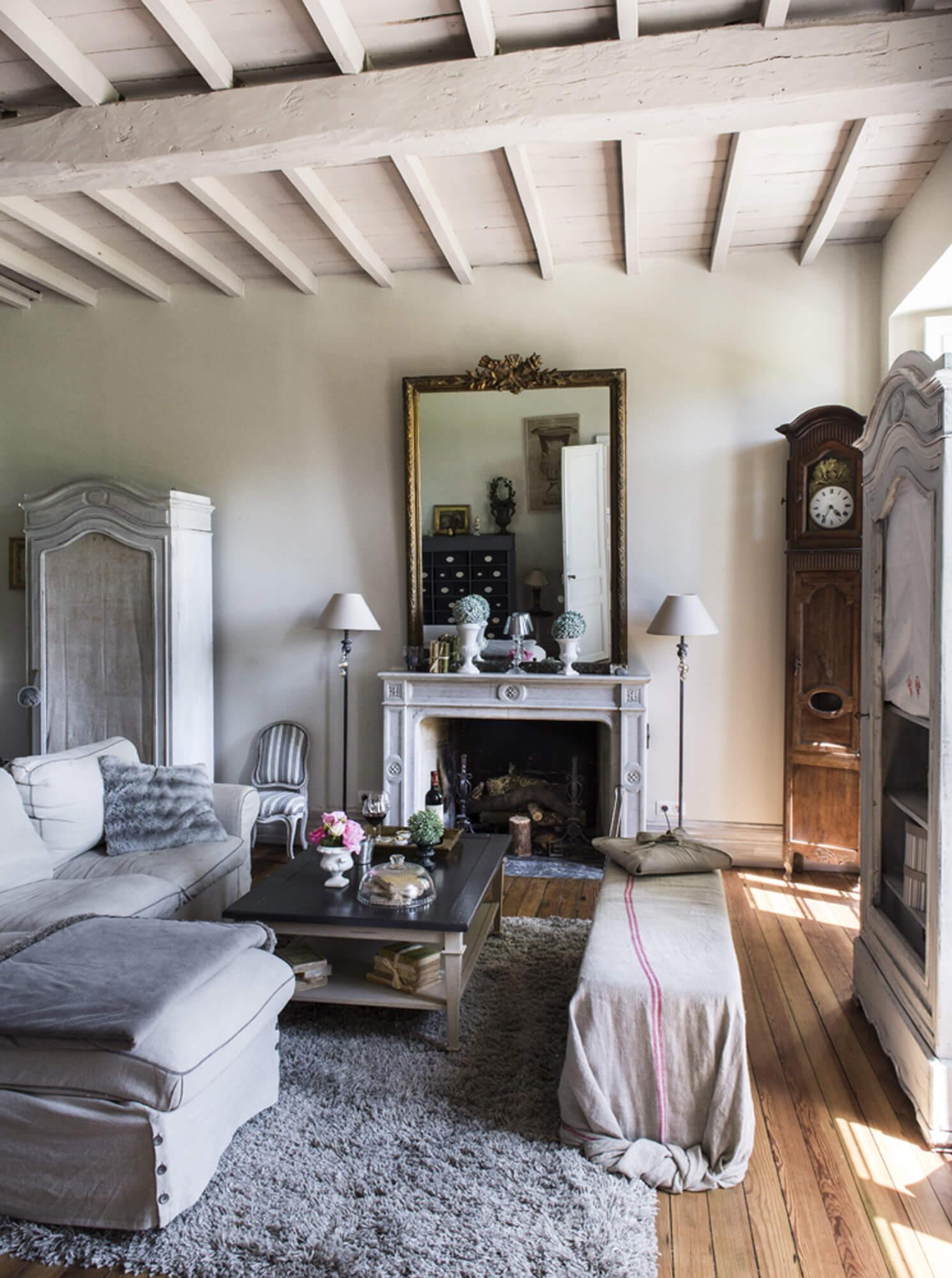 Salon avec canapé, table basse, cheminée traditionnelle et ancienne horloge dans la maison d'hôtes Le Clos Marcamps en Aquitaine