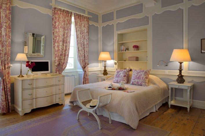 Chambre décorée de façon romantique avec petit-déjeuner servi au lit à l'hôtel La Baronnie Hôtel & Spa