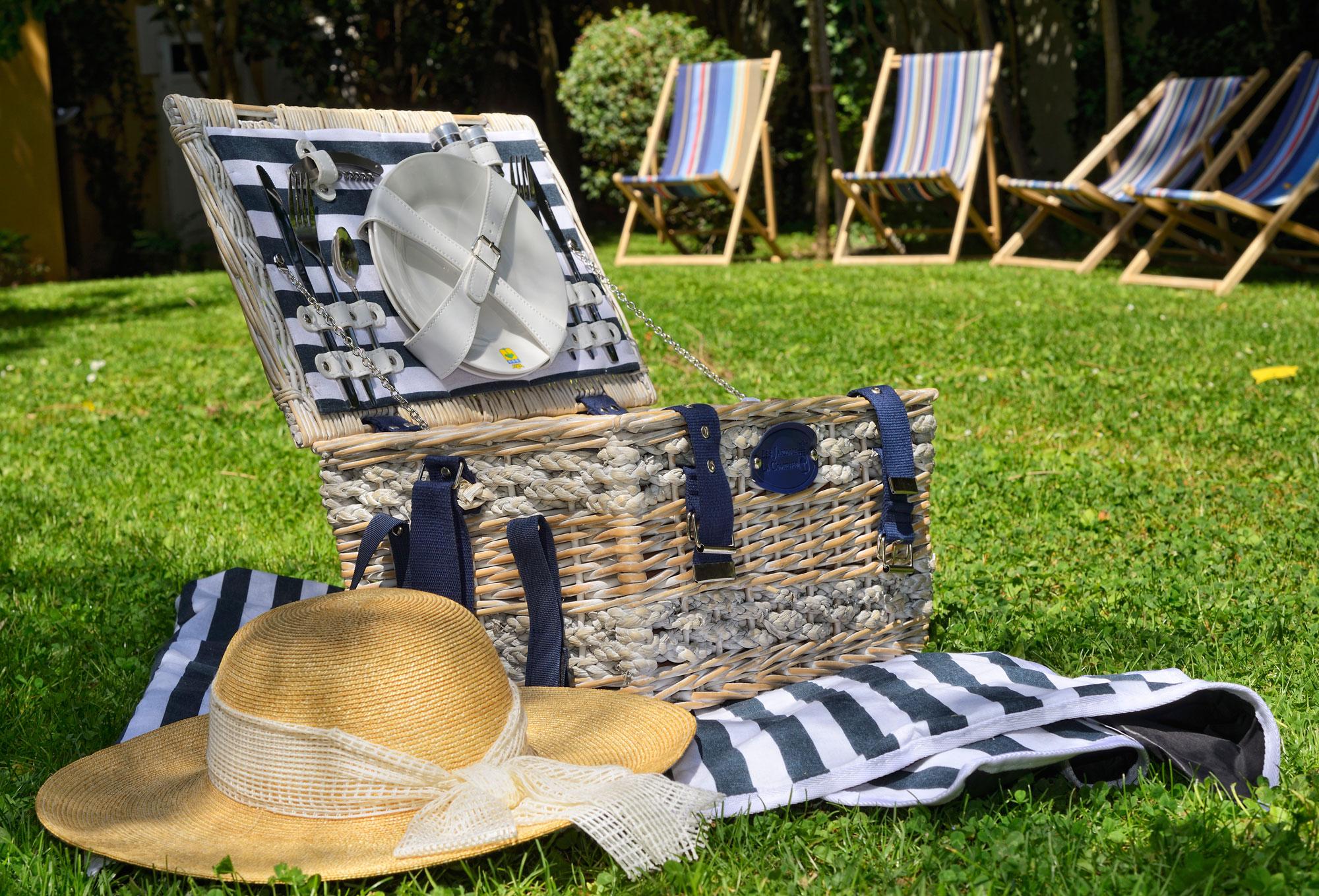 Panier de pique-nique avec chapeau estival sur de l'herbe