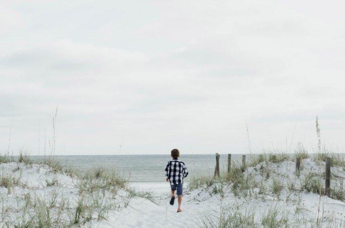 Enfant courant dans les dunes lors d'un week-end en famille