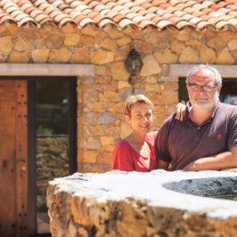 Couple de quinquagénaires accoudés sur une fontaine en pierres, prenant la pose devant une bâtisse de type maison d'hôtes, avec en premier plan une bouteille de vin de la propriété