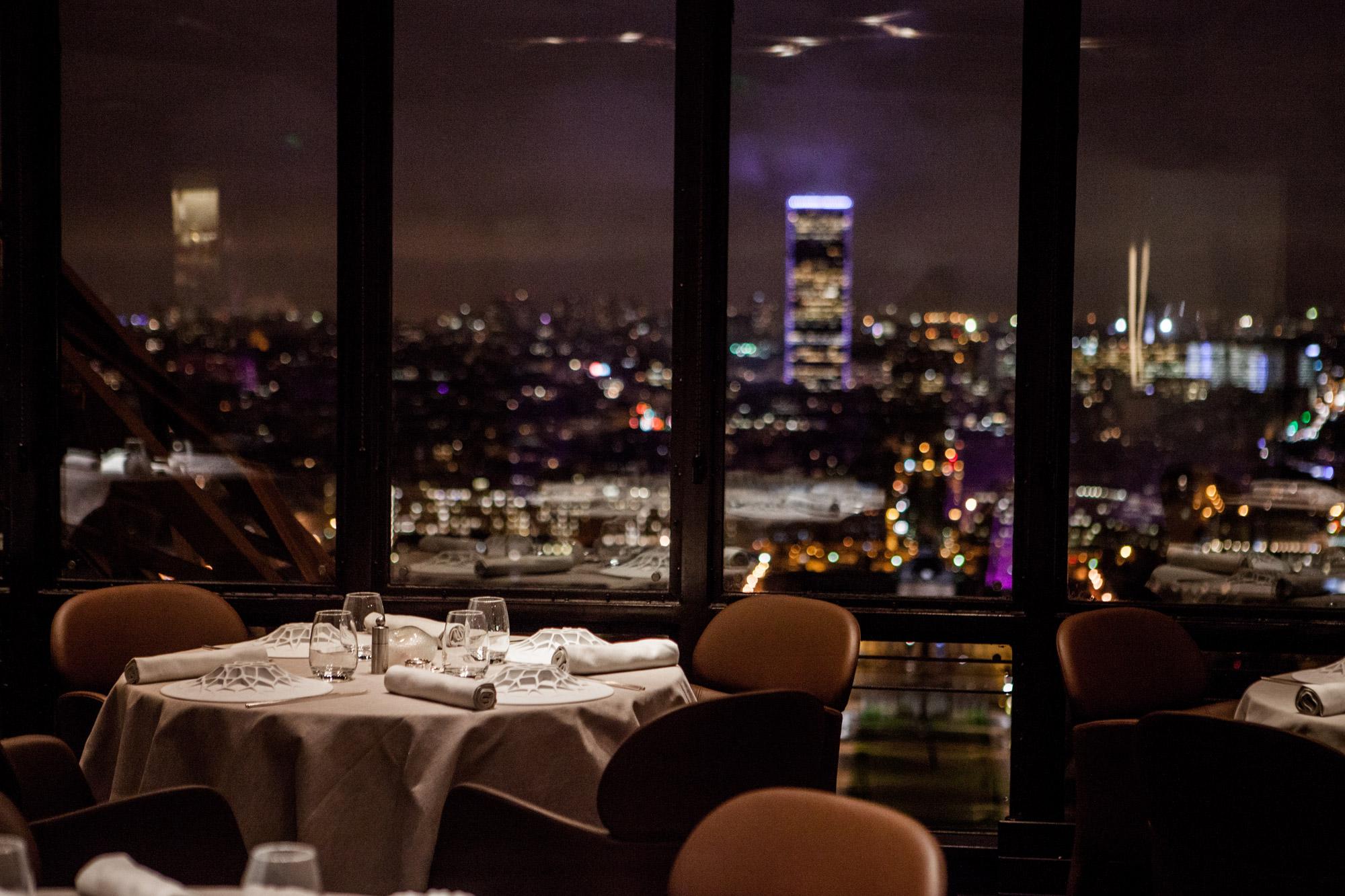 Table dressée pour dîner au Jules Verne, restaurant de la Tour Eiffel, vue panoramique de nuit